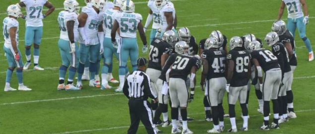 The Oakland Raiders huddle during game against the Miami Dolphins.